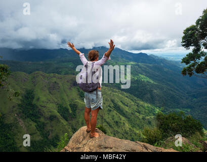 Young caucasian woman hiker with backpack standing on top of the mountain and enjoying valley view in Ella peak - Stock Photo
