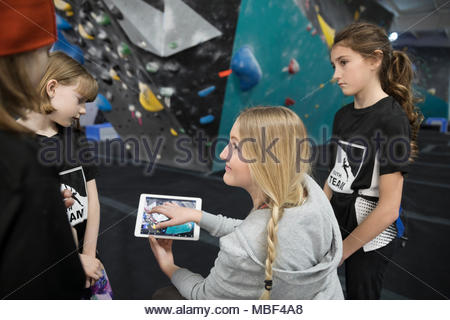 Female instructor with digital tablet giving rock climbing lesson to students at climbing wall in climbing gym - Stock Photo