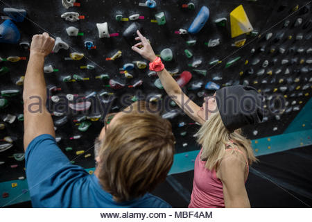 Rock climbers talking, pointing up at climbing wall in climbing gym - Stock Photo