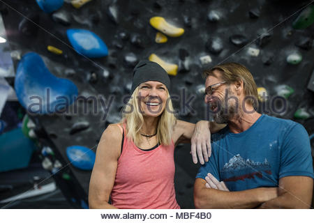 Happy, confident mature couple rock climbers at climbing wall in climbing gym - Stock Photo