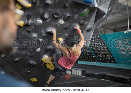 Strong, tough mature female rock climber climbing wall at climbing gym - Stock Photo