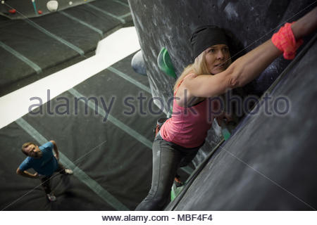 Focused, determined, strong mature female rock climber climbing wall at climbing gym - Stock Photo