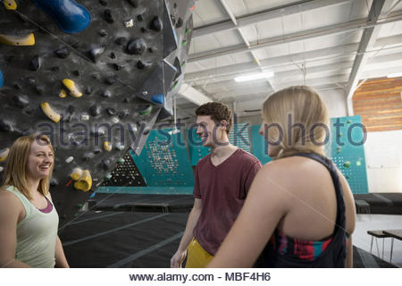 Happy rock climber friends talking at climbing wall in climbing gym - Stock Photo