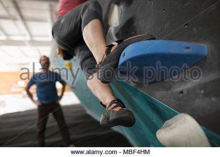 Close up rock climber stepping, climbing wall at climbing gym - Stock Photo