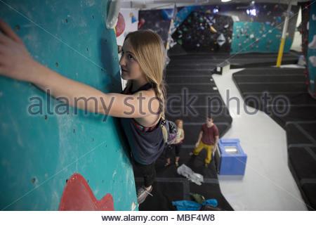 Focused female rock climber climbing wall at climbing gym - Stock Photo