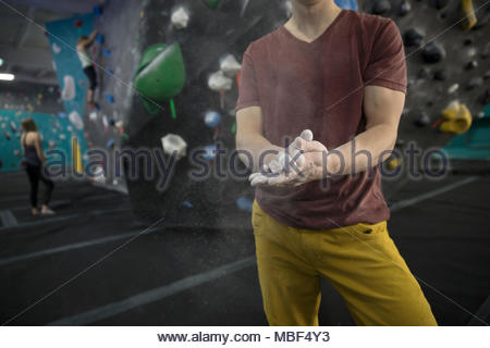 Male rock climber chalking hands, preparing for rock climbing at climbing gym - Stock Photo