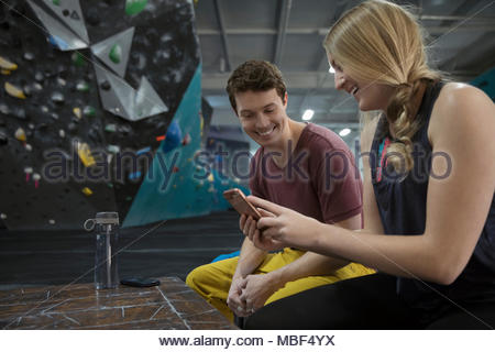 Rock climbers using smart phone at climbing gym - Stock Photo