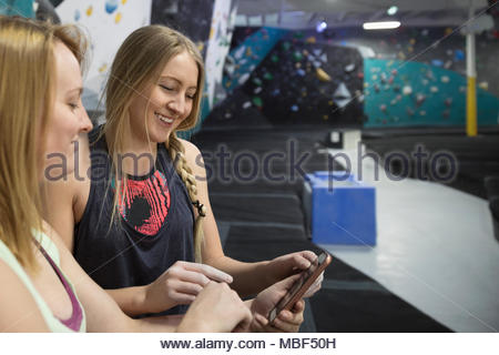 Smiling female rock climbers watching training video on smart phone in climbing gym - Stock Photo