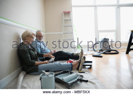 Senior couple preparing to paint in living room, looking at paint swatches, DIY - Stock Photo