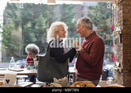 Affectionate couple holding hands in shop - Stock Photo