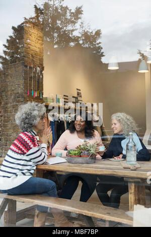 Women friends drinking tea in cafe shop window - Stock Photo