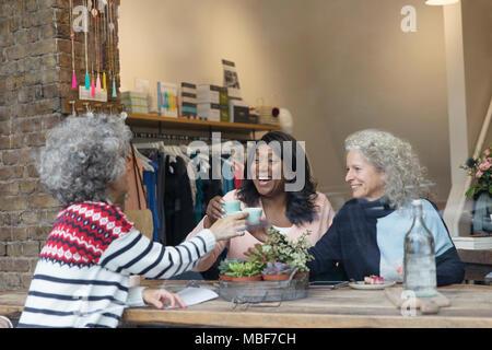 Women friends drinking tea in shop window - Stock Photo