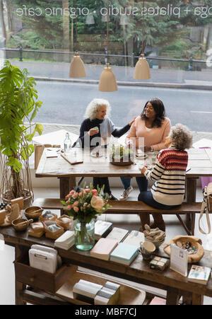 Women friends talking, drinking tea in shop - Stock Photo