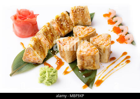 Sushi Japanese food in a restaurant. Japanese restaurant menu. Roll in an omelette isolated on white background. Sushi roll turned on a white backgrou - Stock Photo