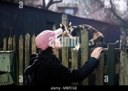 A girl in a pink baseball cap and a black jacket next to a stray cat on an old green fence. Minsk, Belarus. - Stock Photo