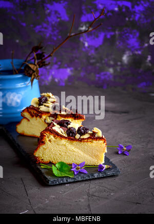 two pieces of cheesecake poured with chocolate and decorated with dried cherry berries on a black background - Stock Photo