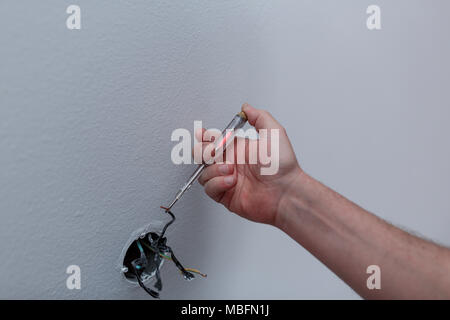 hands of an electrician installing new electrical switches during the house renovation - Stock Photo