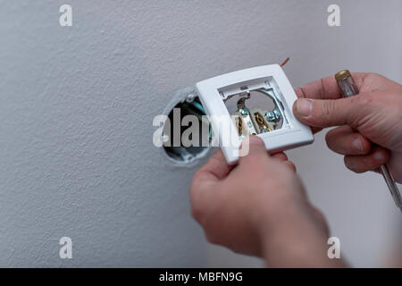 Electrician attaching wires to socket in new building, close up - Stock Photo