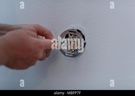 Electrician man at work on switches and sockets of a residential electrical system. - Stock Photo