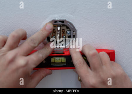 Close up of electrician man at work on switches and sockets of a residential electrical system. - Stock Photo