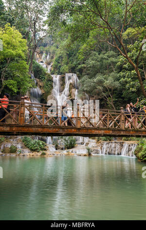 Few tourists taking photos on a bridge in front of the main fall at the Tat Kuang Si Waterfalls near Luang Prabang in Laos. - Stock Photo