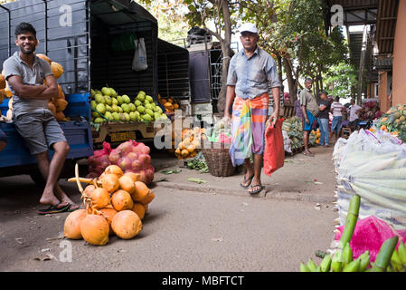 Horizontal view of delivery men at Dambulla Fruit and Vegetable wholesale market in Sri Lanka. - Stock Photo
