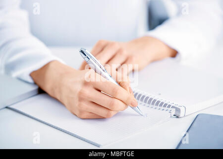Close-up shot of businesswoman's hand holding pen and writing something to the notebook while sitting at office desk. - Stock Photo