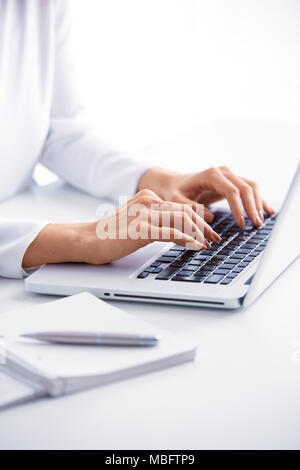 Close-up of businesswoman's hand typing on the keyboard while sitting at office desk. - Stock Photo