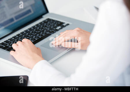Close-up of businesswoman's hand typing on laptop's keyboard while sitting at desk and working on new project. Isolated on white bakcground. - Stock Photo