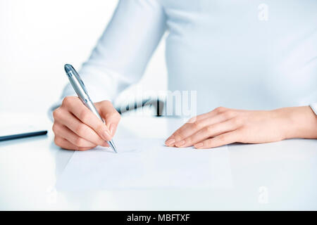 Close-up shot of businesswoman's hand holding pen and sign the paper while sitting at office desk. - Stock Photo
