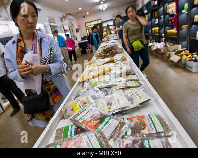 Horizontal view of Japanese tourists shopping in an Ayurvedic shop in Sri Lanka. - Stock Photo