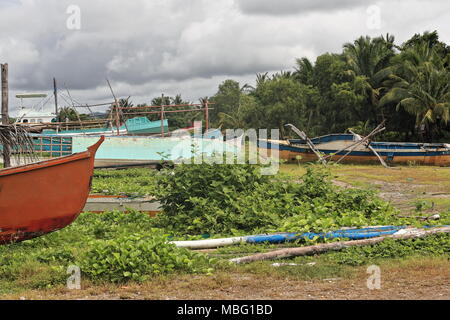 Deserted balangay or bangka boats-fishing and tourist service-out of order stranded on the Polacion barangay beach-covered in nipa palm leaves. Sipala - Stock Photo