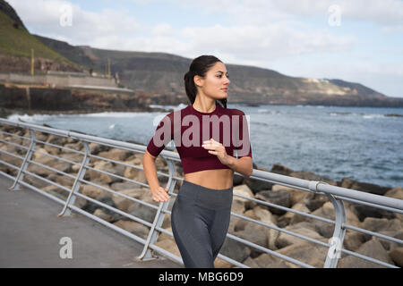 Pretty brunette jogging by the sea wearing maroon shirt and grey thights with hair tied back - Stock Photo
