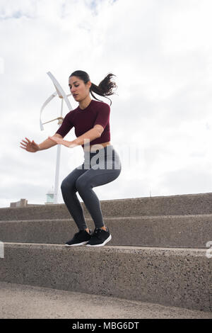 Pretty young female exercising on stairs wearing fitness clothes and her hair tied back - Stock Photo