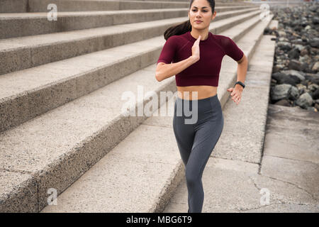 Attractive young brunette running on stairs wearing sports clothing with hair tied back