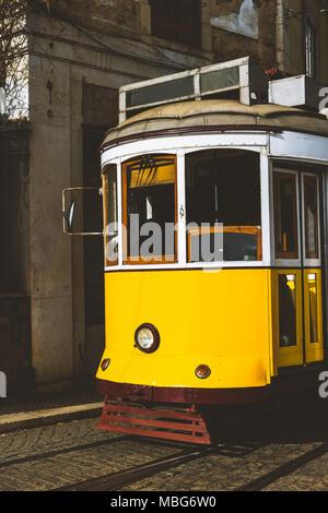Quaint yellow tram on the rails of old and beautiful street of Alfama District of Lisbon. City touristic landmarks of Lisboa Lissabon - Stock Photo