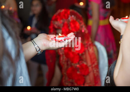 Holding hands on henna candle . She holds the candle in his hand Henna party - Stock Photo
