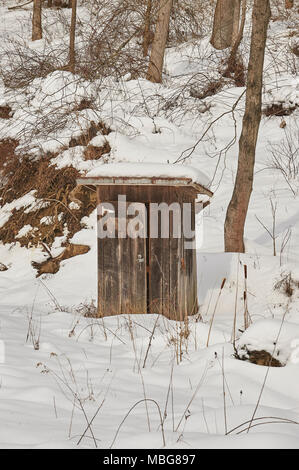 wooden, worn, old outdoor privy in snow - Stock Photo