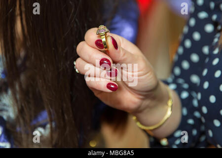Woman holding a ring in his hand, picture has a shallow depth of field so his face is not recognizable - Stock Photo
