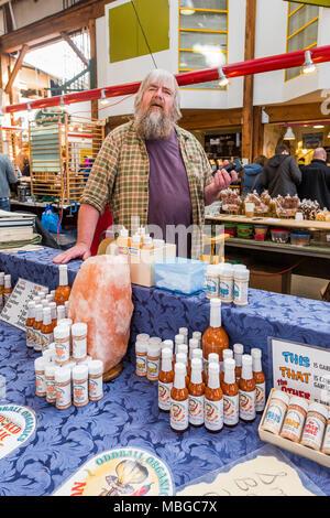 Randy of Oddball Organics, sells his garlic sauces at Granville Island Public Market, Vancouver, British Columbia, Canada. - Stock Photo