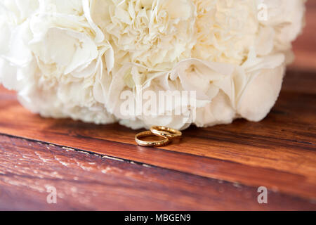 a closeup of two golden rings in front of the bridal bouquet on a wooden table - Stock Photo