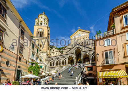 ourists walk the long staircase to the 9th century Roman Catholic Amalfi Cathedral dedicated to St Andrew on a summer day on the Amalfi Coast of Italy - Stock Photo