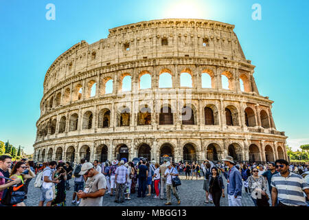 Crowds of tourists wait outside the ancient Colosseum on a sunny afternoon in Rome Italy - Stock Photo