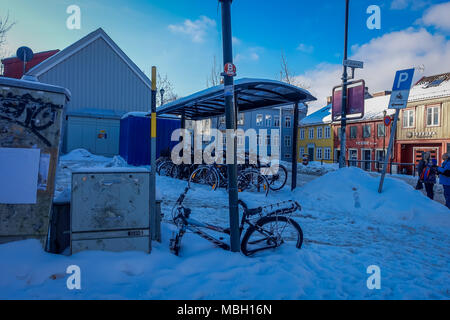 TRONDHEIM, NORWAY - APRIL 04, 2018: Unidentified people in the streets and row of bikes under a bus stop close to traditional Scandinavian wooden houses stand along the street in Trondheim - Stock Photo