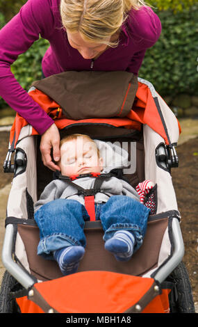A mother sits on the front stairs talking on her cell phone while a baby boy sleeps in a running stroller. - Stock Photo