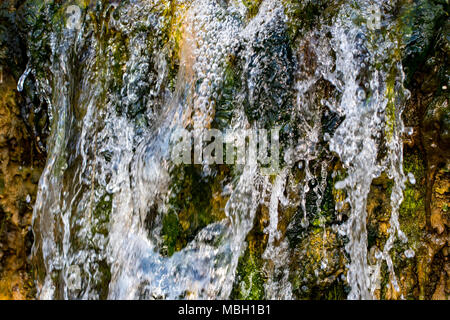 Quickly flowing mountain stream, close-up flowing water from the rock. - Stock Photo