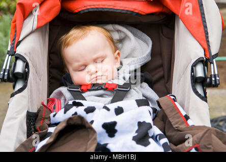 A 10 month old baby boy asleep in his stroller. - Stock Photo