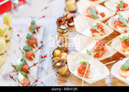 Delicious rolls canapes of eggplant and tomato. Tasty buffet table. Summer party outdoor. Catering concept - Stock Photo