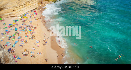 CARVOEIRO, PORTUGAL - AUGUST 25, 2016: Aerial view of tourists sunbathing on Carvoeiro beach in Portugal - Stock Photo