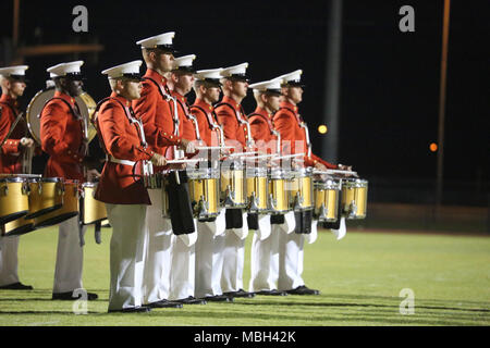 "Marines with ""The Commandant's Own,"" U.S. Marine Drum & Bugle Corps, perform during a West Coast tour performance at Arizona Western College (AWC), Yuma, Az., March 8, 2018. The West Coast tour is conducted to showcase the new drill sequences implemented andreach an audience that is typically lapsed during the annual parade season. - Stock Photo"